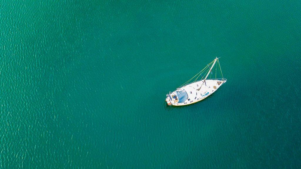 En segelbåt på grönt vatten